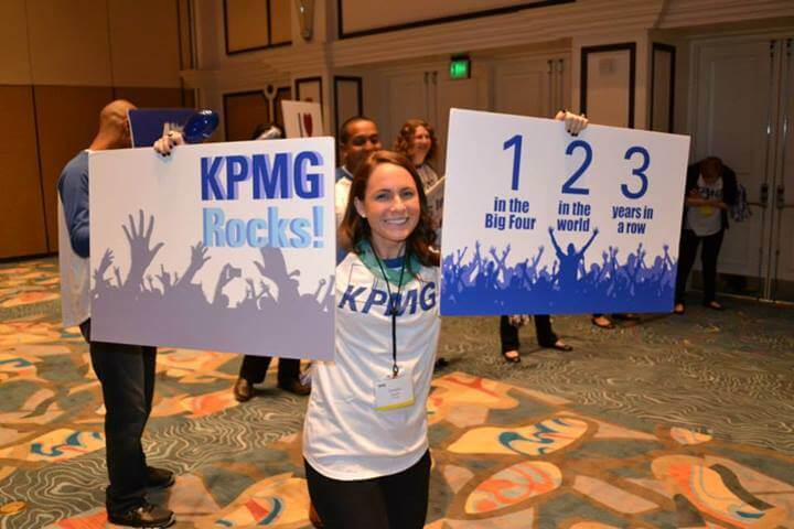 KPMG Rocks signs held by a woman in a KPMG shirt
